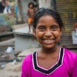 India - Slums - One Child - Girl smiles water filters